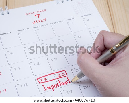 Woman writing word important on right hand by pen in calendar desk with red ink