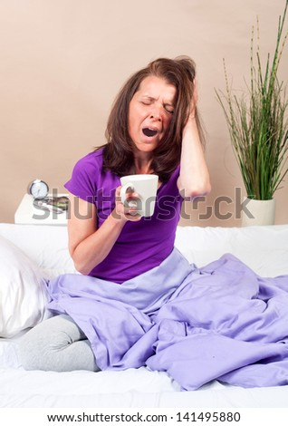 Woman yawing sitting in her bed with a coffee cup in her hand - stock photo