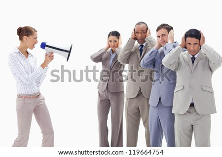Woman yelling through a megaphone at business people with their hands on their ears against white background - stock photo