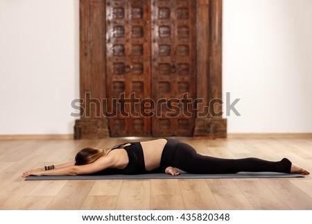 Woman yoga trainer in kapotasana (pigeon) pose - stock photo