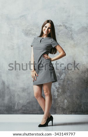 Woman young full length studio with long beautiful legs and long hair on gray background posing  in dress