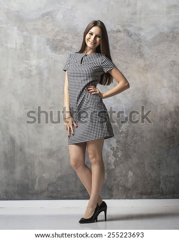 Woman young full length studio with long beautiful legs and long hair on grey background posing  in dress and high heel shoes