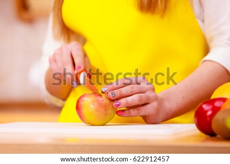 Woman young housewife in kitchen at home preparing fresh salad slicing apple fruits on cutting board. Healthy eating, cooking, vegetarian food, dieting and people concept