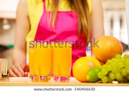 Woman young housewife in kitchen making fresh orange juice. Healthy eating, vegetarian food, dieting and people