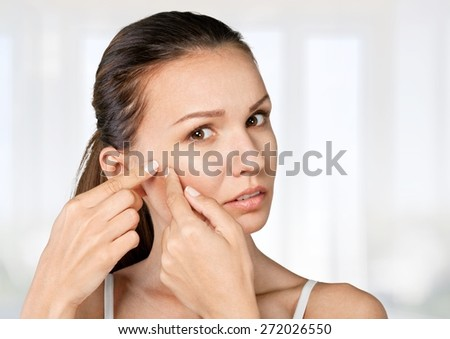 Woman. Young woman squeezing pimple on her cheek on white background - stock photo