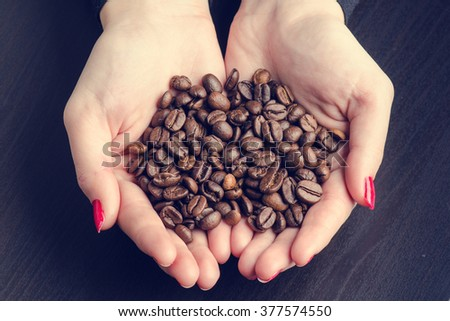 Womanas hand keep coffee beans on a dark background.      Coffee beans on a black background. Raw coffee beans. Grained product. Hot drink. Close up. - stock photo