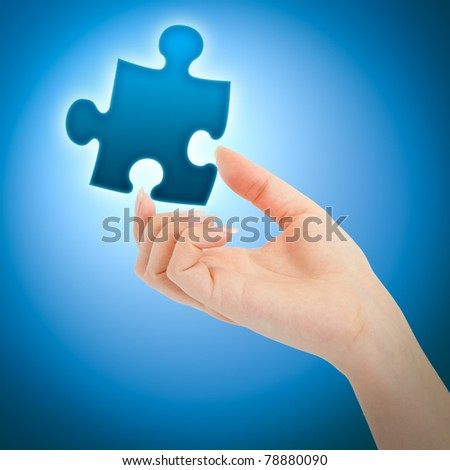 Womanish hand with a blue shining piece of puzzle on blue background