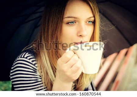 womanl drinks fragrant coffee with pleasure under umbrella in bad weather