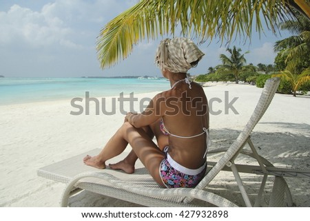 Womanl on a sun lounger under a palm tree in the Maldivian beach - stock photo