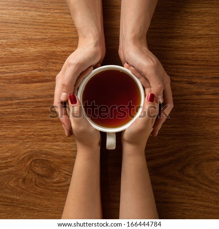 Womans and mens hands holding hot cup of tea on wooden table - stock photo