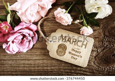 Womans Day message with rustic pink roses on wooden table - stock photo