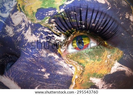 womans face with planet Earth texture and ethiopian flag inside the eye. Elements of this image furnished by NASA. - stock photo