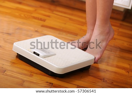 Womans feet near to a scale - stock photo