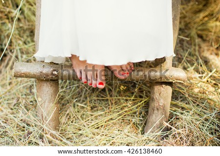 womans feet on dry grass - stock photo