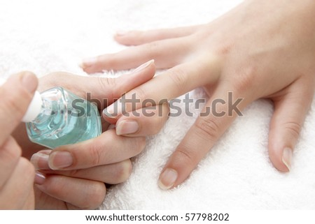 womans finger nails having clear varnish applied on white towel
