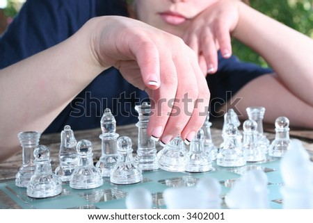womans hand and chessboard - stock photo