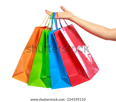 Womans hand holding colorful shopping bags isolated on white background - stock photo