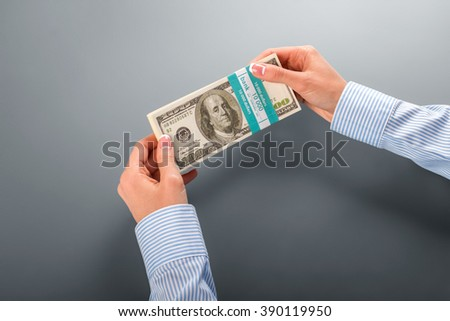 Womans' hand holding dollar bundle. Female employee holds money bundle. So fresh and nice. Not bad for first salary. - stock photo
