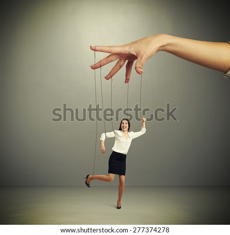 womans hand manipulating puppet over dark background - stock photo