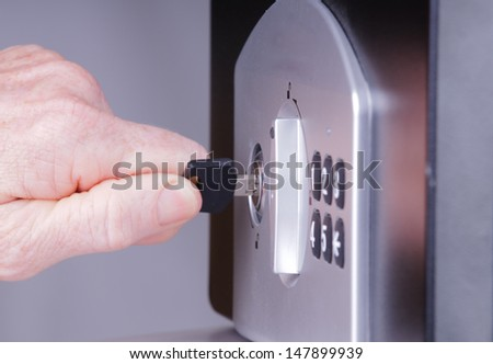 Womans hand using a key to open a safe or vault