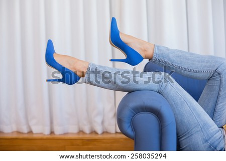 Womans legs in high heels in the living room - stock photo