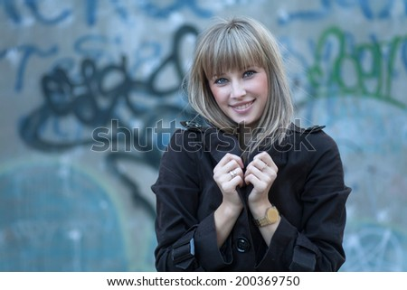 Women against grungy wall smiling, a lot of copyspace - stock photo