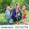 women and  baby girls planting raspberry in garden - stock photo