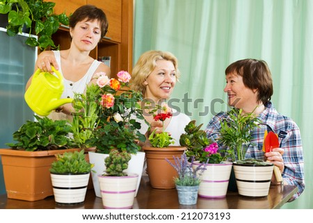women and girl taking care of domestic plants