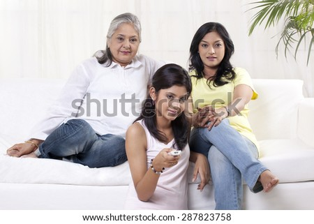 Women and girl watching television - stock photo
