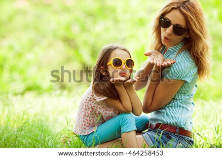 Women and kids fashion concept. Portrait of beautiful mother and daughter wearing trendy eyewear, sitting in green grass, sending air kiss at camera. Copy-space
