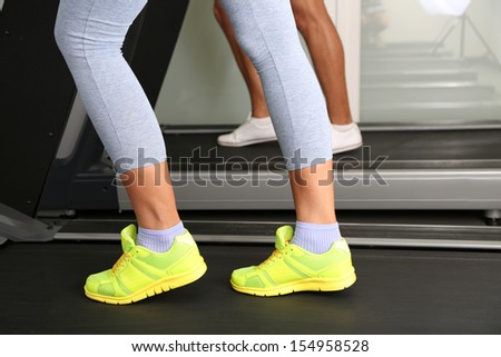 Women and men feet on treadmill close-up - stock photo