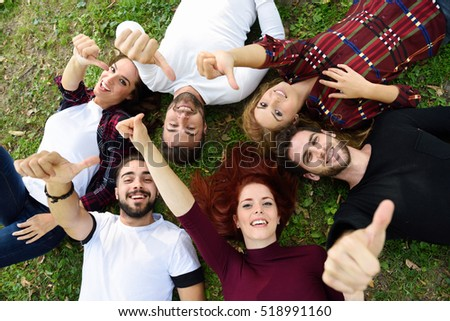 Women and men laying on grass wearing casual clothes. Group of young people together outdoors in urban park.