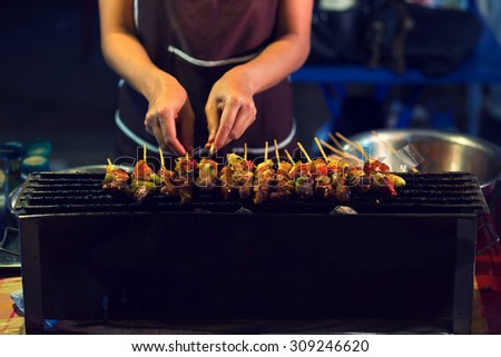Women are grilling BBQ for sale , motion blurred
