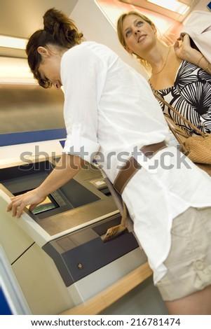 Women at an ATM machine. - stock photo