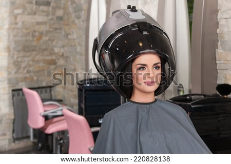 women at hairdresser while drying under hairdryer. Portrait of woman under hairdressing machine in parlor - stock photo
