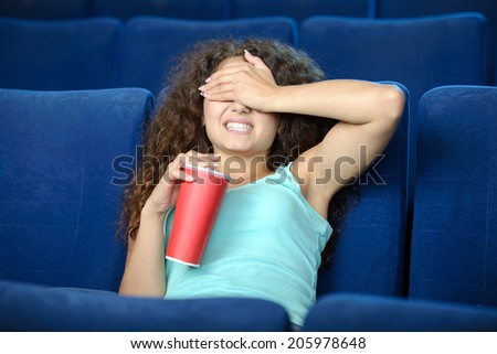 Women at the cinema. Beautiful young women drinking soda while watching movie at the cinema - stock photo