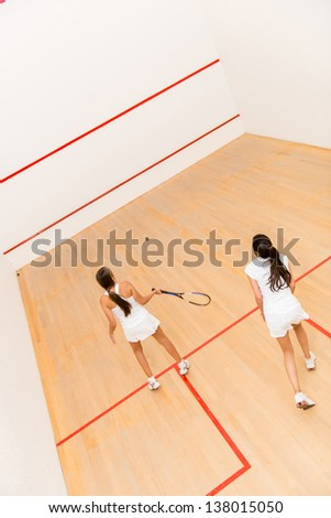 Women at the court playing a match of squash - stock photo