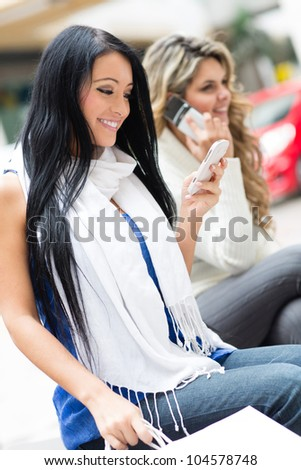 Women at the shopping center using their phones - stock photo