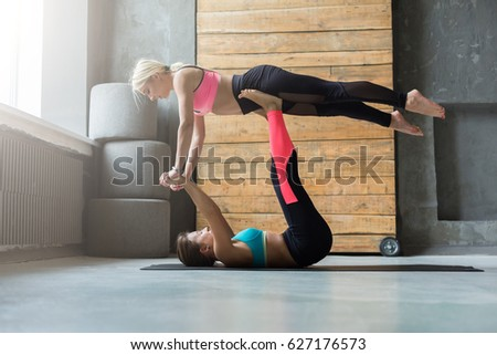 Women Balancing In Yoga Pose Acroyoga With Partner Two Athletic Flexible Girls Sportswear