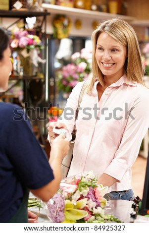 Women being served at florist - stock photo