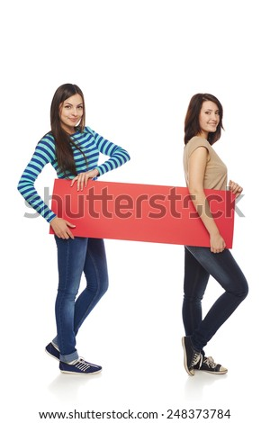 Women billboard sign. Fill length of two young beautiful women smiling carrying blank red placard, over white background - stock photo