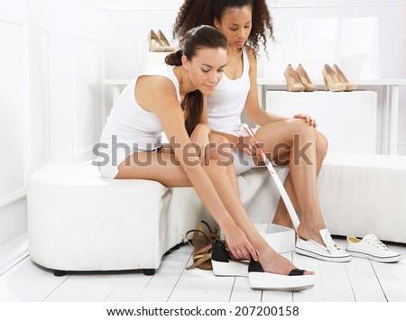 Women buy shoes .Women buy shoes at a shoe store, mulatto and Caucasian  - stock photo