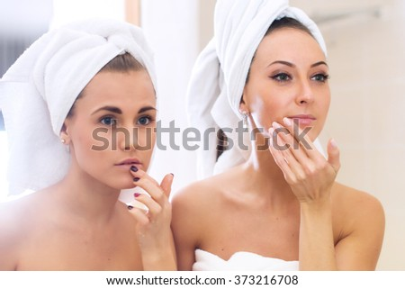 Women caring of their faces looking into mirror. reflection beautiful girls  - stock photo