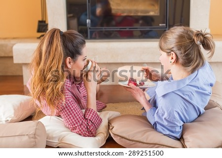 Women chitchatting with best friend at home near a tea.