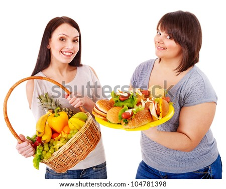 Women choosing between fruit and hamburger. Isolated. - stock photo