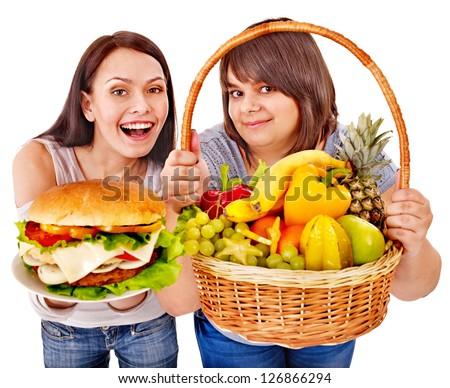 Women choosing between fruit and hamburger. Isolated. - stock photo