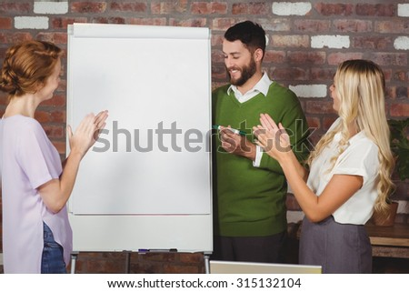 Women clapping for male colleague during presentation - stock photo