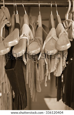 women clothes hanging on a rack clothes store, selective focus on center, sepia photo