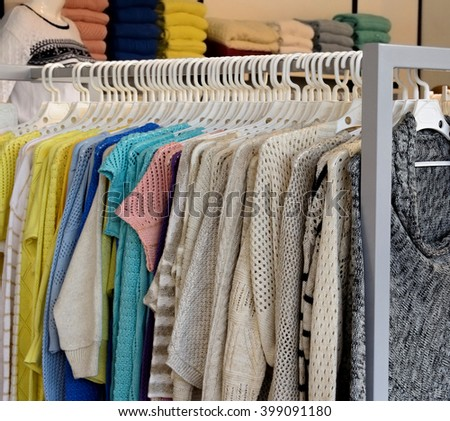Women clothing hang on hangers inside of a shop. - stock photo