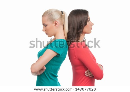 Women confrontation. Two angry women standing back to back and holding their arms crossed while isolated on white - stock photo